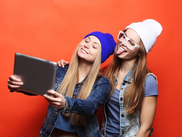 Amigos de menina hipster tomando selfie com tablet digital