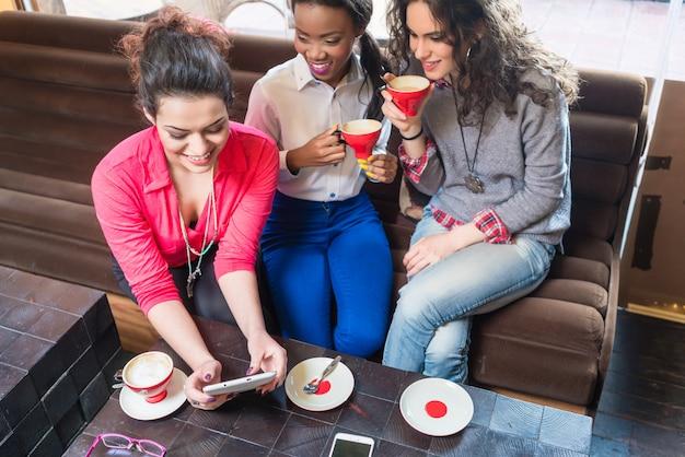 Amigos de menina sentados juntos no café e mostrando fotos no telefone inteligente