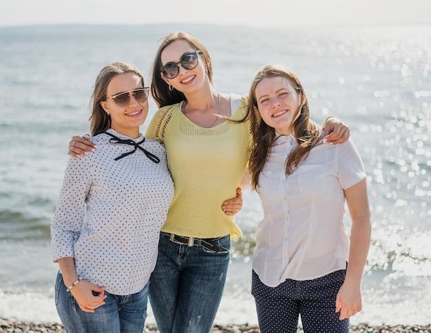 Amigos de menina vista frontal à beira-mar