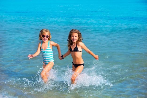 Amigos de meninas crianças correndo juntos na costa da praia