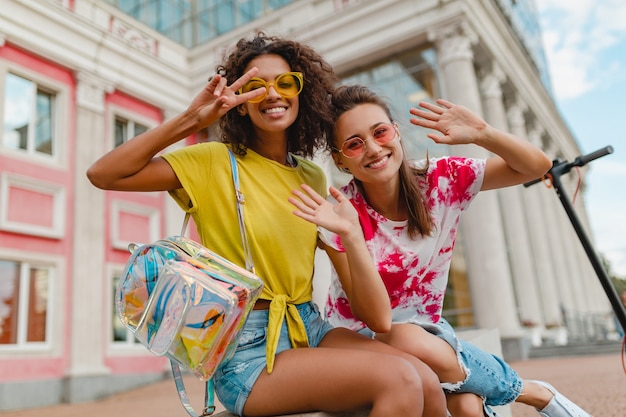 Amigos de meninas felizes e elegantes sorrindo sentados na rua, mulheres se divertindo juntas