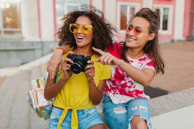 Amigos de meninas felizes sorrindo sentados na rua com uma câmera fotográfica, mulheres se divertindo juntas