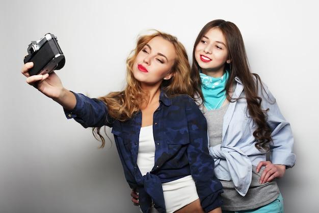 Amigos de meninas felizes tirando algumas fotos em cinza