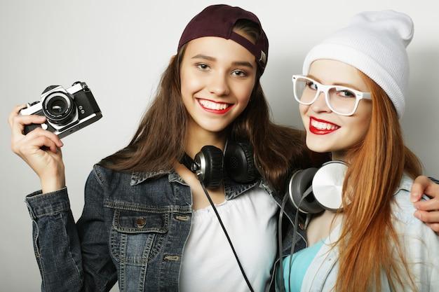 Amigos de meninas felizes tirando algumas fotos, sobre fundo cinza