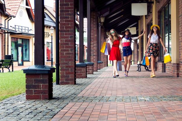 Amigos de meninas femininas muito felizes mulheres brilhantes em vestidos coloridos, chapéus e sapatos de salto altos com sacos de compras, andando na rua depois das compras
