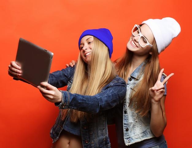 Amigos de meninas hipster tomando selfie com tablet digital, estúdio
