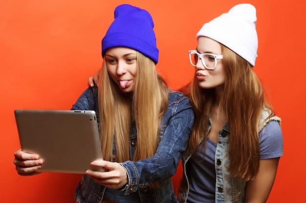 Amigos de meninas hipster tomando selfie com tablet digital