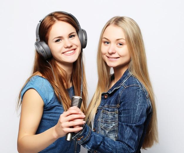 Amigos de meninas jovens com microfone