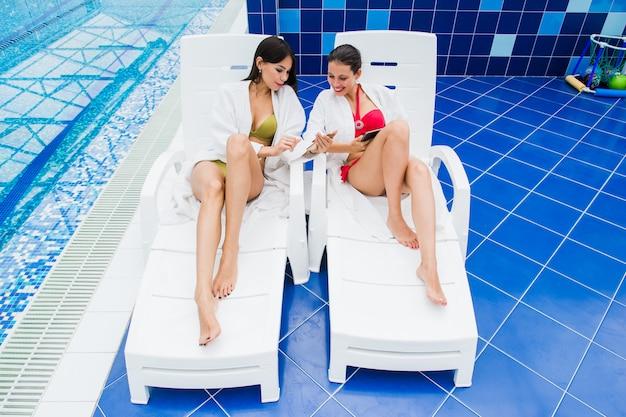 Amigos de meninas jovens mensagens com o amigo em seu smartphone. spa de relaxamento e conceito de redes sociais de tecnologia.
