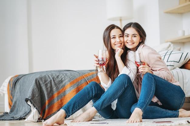 Amigos de meninas jovens morena despreocupada em casual com taças de vinho se divertindo juntos na festa em casa