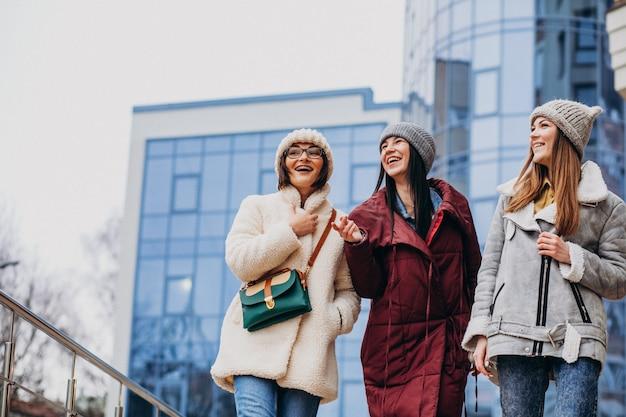 Amigos de meninas reunidos em tempo de inverno fora da rua
