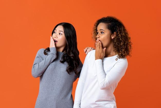 Amigos de mulher de raça mista em gesto de choque