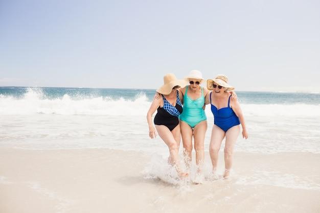 Amigos de mulher sênior brincando na água
