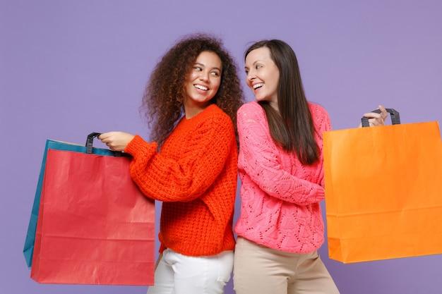 Amigos de mulheres afro-americanas engraçadas em camisolas de malha isoladas na parede roxa violeta. conceito de estilo de vida de pessoas segure a sacola com compras depois das compras, olhando uns para os outros.