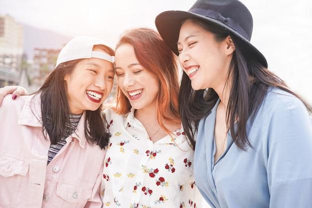 Amigos de mulheres asiáticas se divertindo ao ar livre em um dia ensolarado