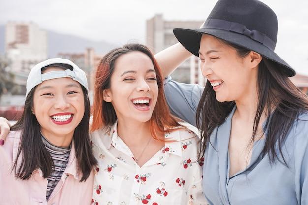Amigos de mulheres asiáticas se divertindo ao ar livre. meninas na moda felizes rindo juntos