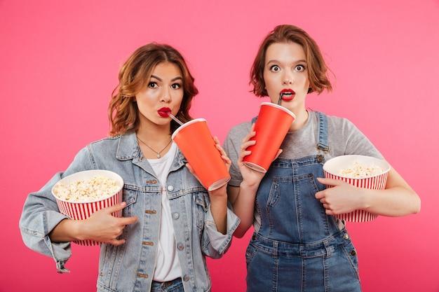 Amigos de mulheres chocados comendo pipoca assistir filme.