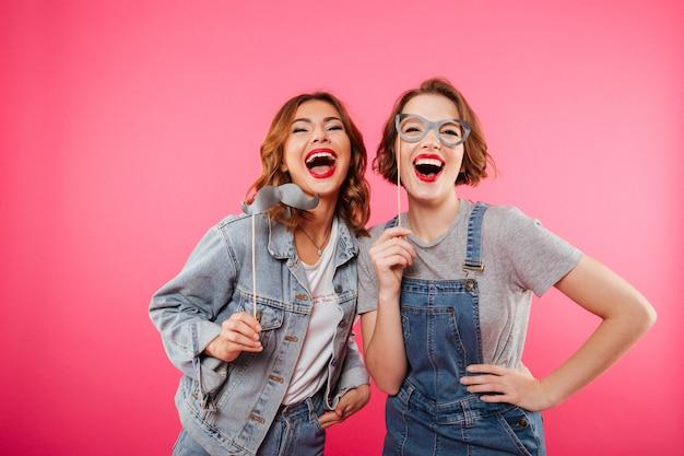 Amigos de mulheres engraçadas segurando óculos e bigode falso.