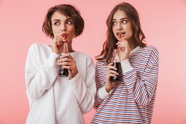 Amigos de mulheres felizes isolados sobre a parede rosa, bebendo refrigerante.