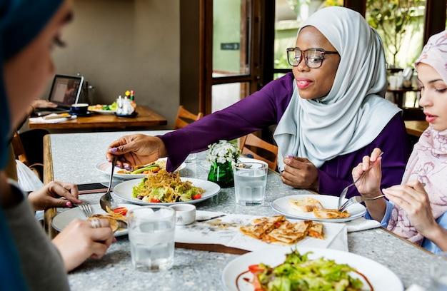 Amigos de mulheres islâmicas jantando juntos com felicidade