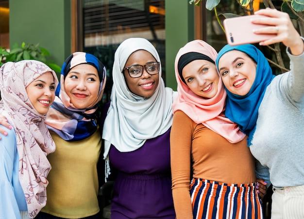 Amigos de mulheres islâmicas tomando selfie juntos