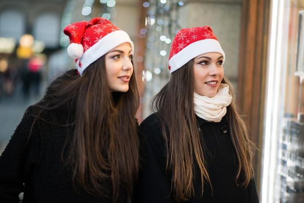 Amigos de mulheres jovens, compras juntos antes do natal