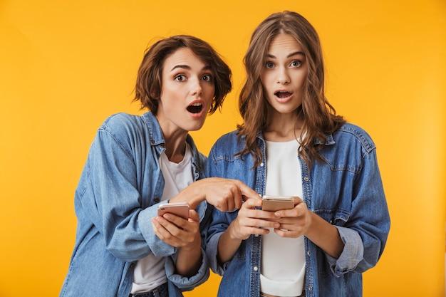 Amigos de mulheres jovens emocionais chocados posando isolados sobre uma parede amarela usando telefones celulares.