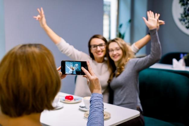 Amigos de mulheres no café dentro de casa. duas amigas lindas mulheres abraçando, com as mãos para cima e posando para a foto juntos, enquanto a terceira mulher amiga está tirando uma foto no smartphone