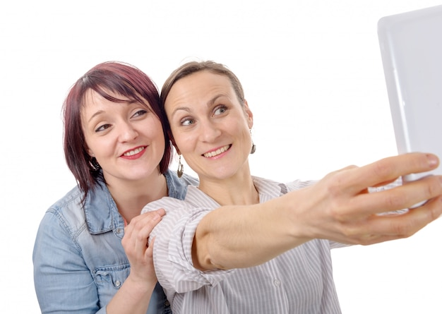 Amigos de mulheres tomando selfie com tablet digital
