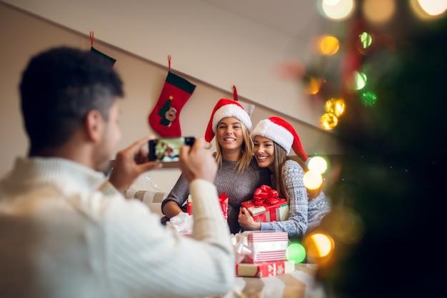 Amigos de natal adoráveis brincalhões felizes com chapéus de papai noel e suéteres desfrutando de casa para as férias.