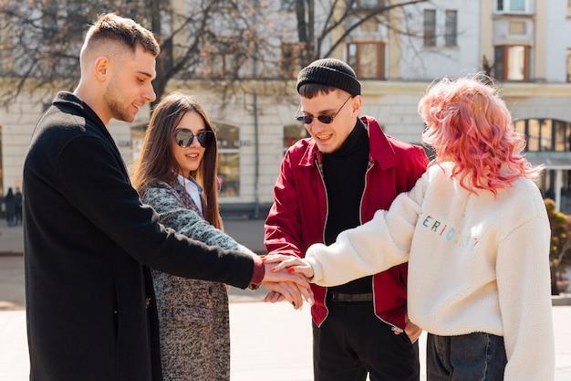 Amigos de pé na rua e de mãos dadas juntos