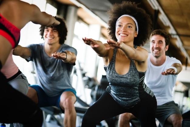 Amigos de pessoas em forma bonita se exercitando juntos na academia