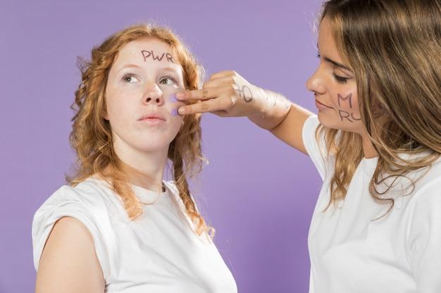 Amigos de pintura mulher close-up enfrentam para protestar