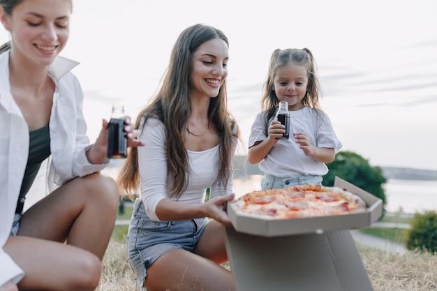 Amigos de piquenique com pizza e bebidas, dia de sol, pôr do sol, companhia, diversão, casais e mãe com bebê