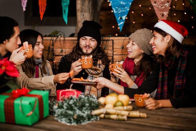 Amigos de posada mexicana comemorando o natal no méxico e bebendo ponche