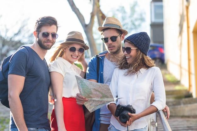 Amigos de quadril lendo o mapa e tirando fotos nas ruas