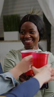 Amigos de raça mista se socializando enquanto compartilham conselhos sobre a mídia social relaxando no sofá tarde da noite na sala de estar