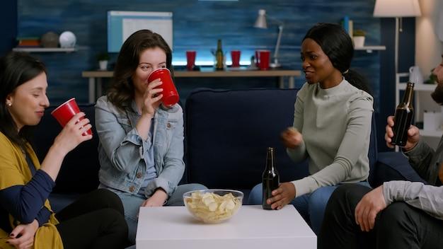 Amigos de raça mista torcendo por garrafas de cerveja, aproveitando o tempo que passam juntos enquanto relaxam no sofá. grupo de pessoas multi-étnicas se divertindo, socializando durante a festa wekeend tarde da noite