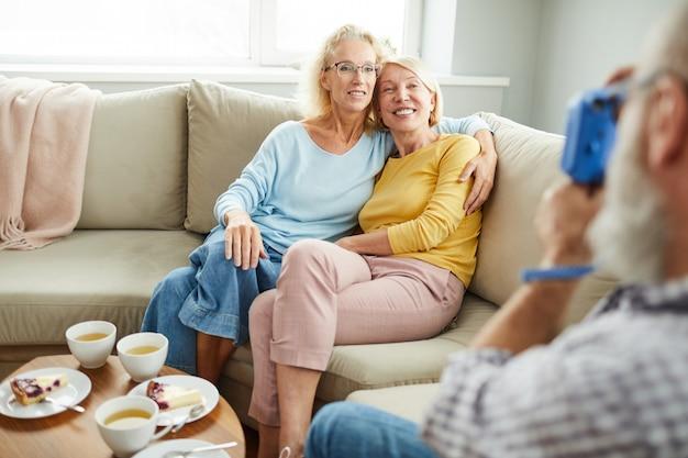Amigos de senhoras felizes abraçando no sofá