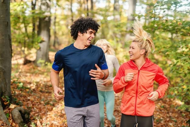 Amigos de sorriso desportivos correndo na floresta no outono. conceito ao ar livre de aptidão.