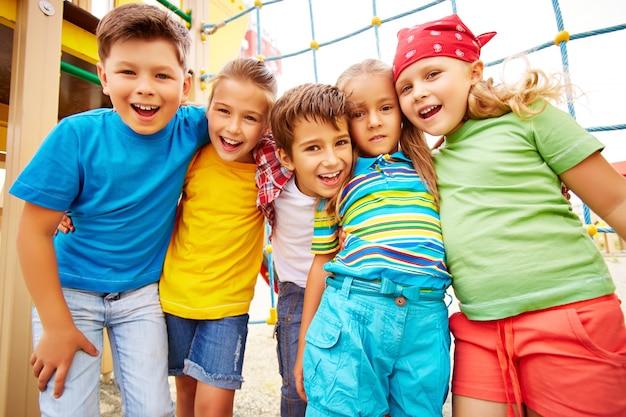 Amigos de sorriso que abraçam no campo de jogos