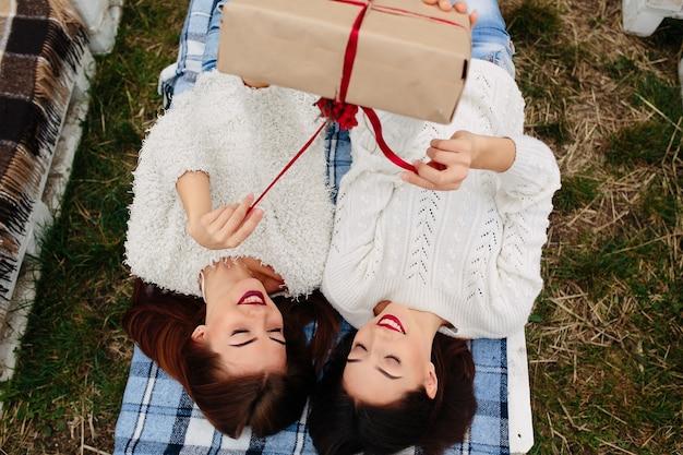 Amigos de sorriso que abre um presente em conjunto