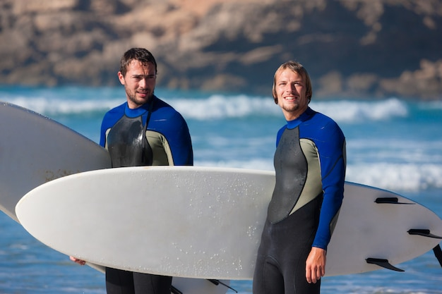 Amigos de surfista com prancha de surf na beira-mar