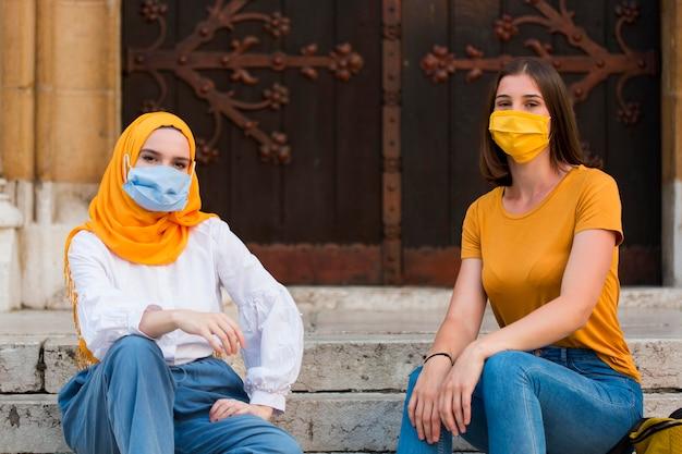Amigos de tiro completo usando máscaras médicas