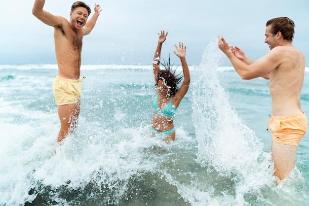Amigos de tiro médio brincando no mar