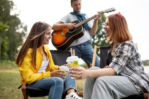 Amigos de tiro médio com bebidas e música
