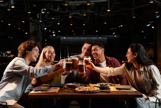 Amigos de tiro médio com canecas de cerveja