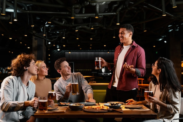 Amigos de tiro médio com cerveja em boteco