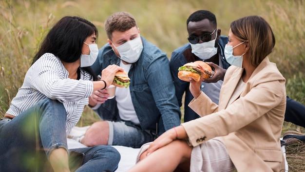 Amigos de tiro médio com hambúrgueres e máscaras