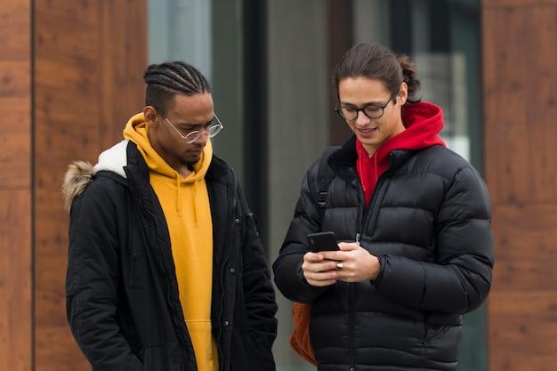 Amigos de tiro médio com smartphone ao ar livre